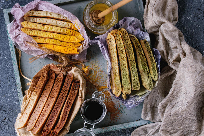 Variety of ombre pancakes. Variety of sliced american ombre chocolate, green tea matcha and turmeric pancakes served in paper paper wrapper with honey sauces on stock image