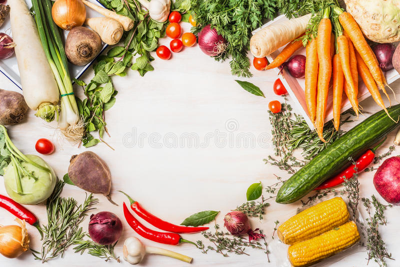 Variety of organic vegetables for tasty vegan or vegetarian cooking on white wooden background, top view, frame. Healthy or diet food concept royalty free stock image