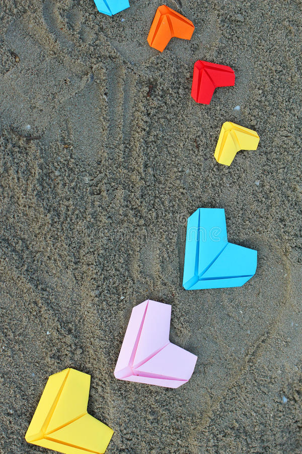 Variety paper hearts. On beach background stock image