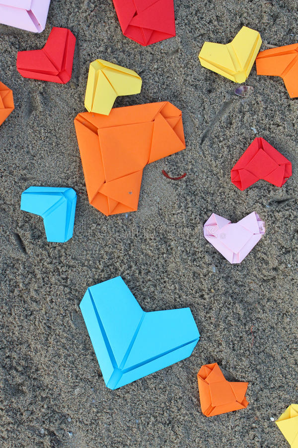 Variety paper hearts. On beach background royalty free stock image