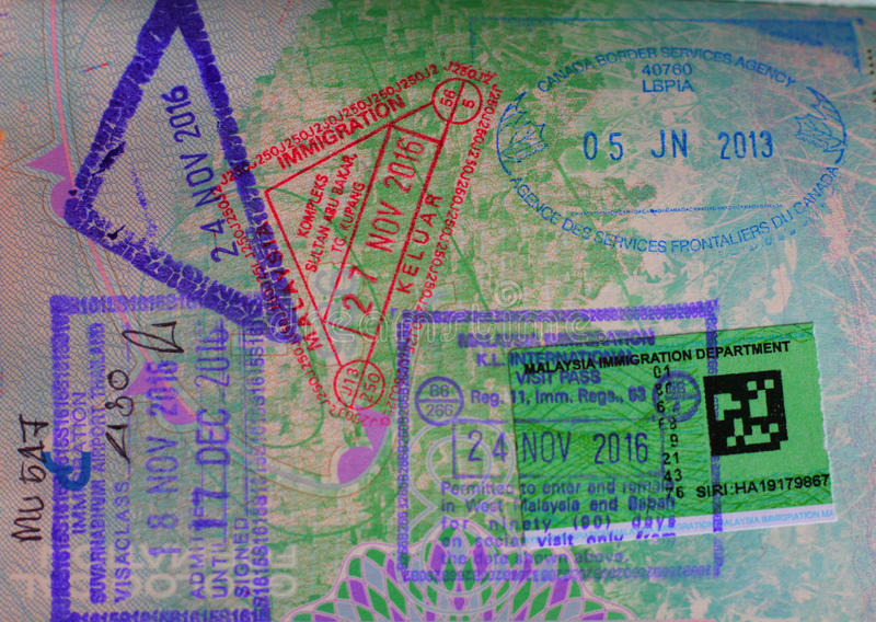 Variety of passport stamps on a passport page. Several different passport stamps on British passport page royalty free stock photos