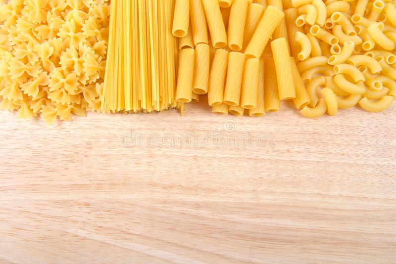 Variety of pasta on a wood table with copy space royalty free stock photography