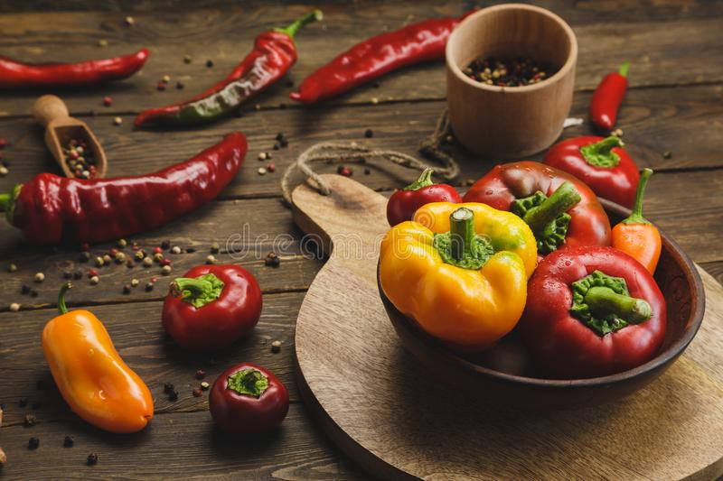 Variety of peppers on a wooden background. stock photo