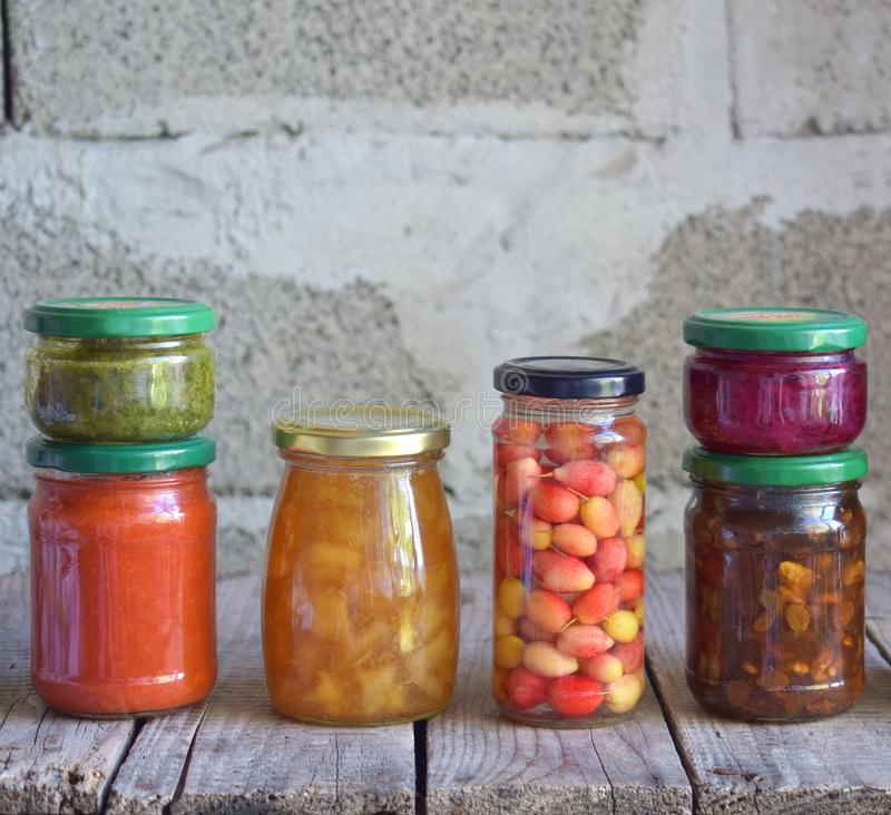 Variety of preserved food in glass jars - pickles, jam, marmalade, sauces, ketchup. Preserving vegetables and fruits. Fermented fo stock image