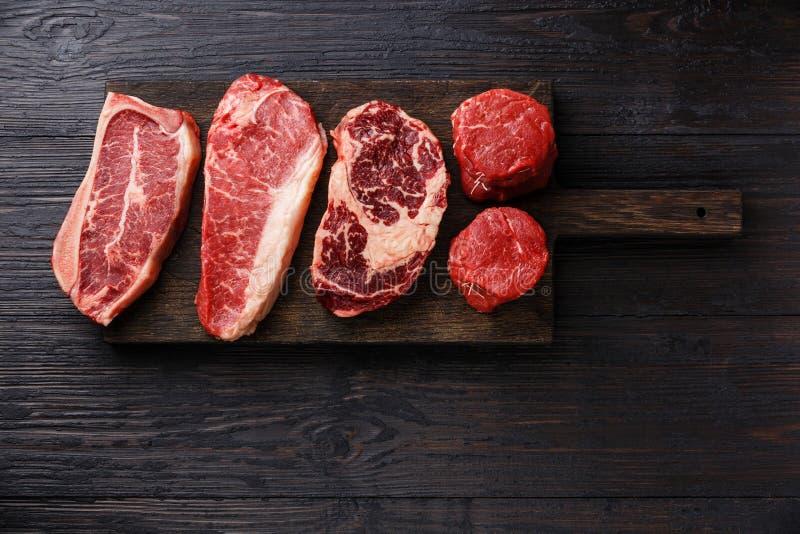 Variety of Raw Prime meat steaks. Variety of Raw Black Angus Prime meat steaks Blade on bone, Striploin, Rib eye, Tenderloin fillet mignon on wooden board copy stock image