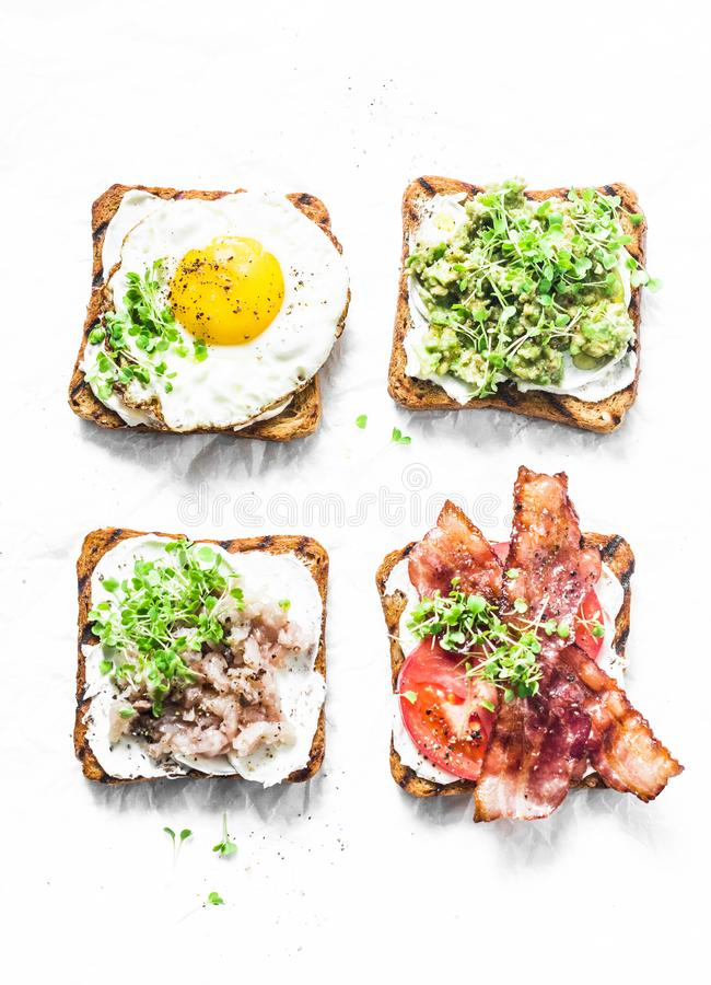 Variety of sandwiches for breakfast, snack, appetizers - avocado puree, fried egg, tomatoes, bacon, cream cheese, smoked mackerel stock images
