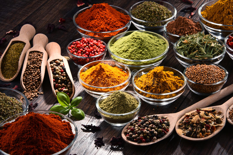 Variety of spices and herbs on kitchen table royalty free stock photos