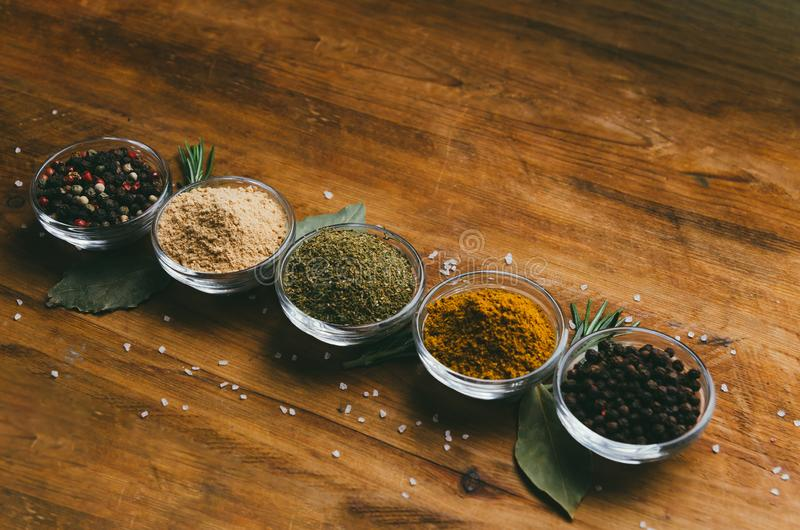 Variety of spices in round glass bowls - ground ginger, hops-suneli, kari, black pepper and mix royalty free stock images