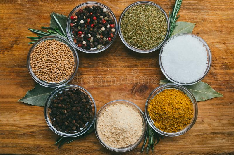 Variety of spices in round glass bowls - ground ginger, hops-suneli, kari, black pepper and mix stock image