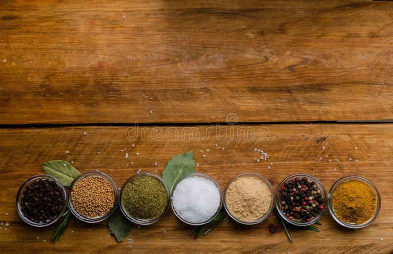 Variety of spices in round glass bowls - ground ginger, hops-suneli, kari, black pepper and a mixture stock image