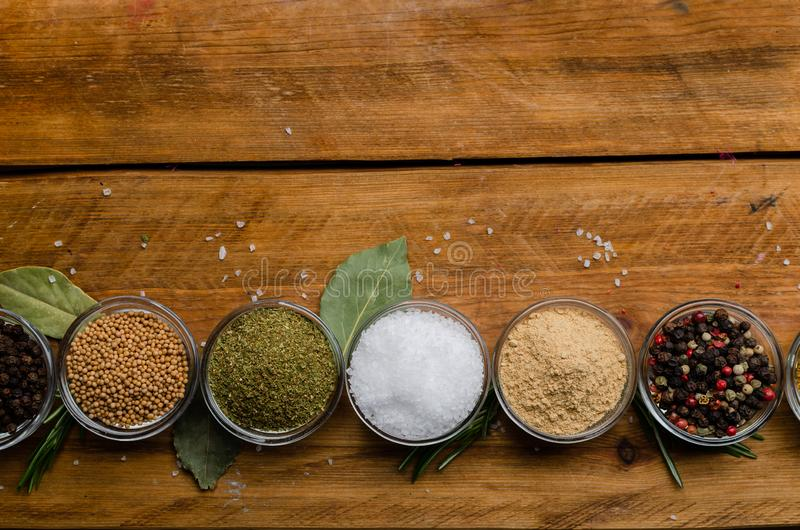 Variety of spices in round glass bowls - ground ginger, hops-suneli, kari, black pepper and a mixture royalty free stock photography