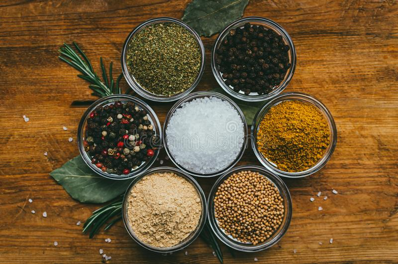 Variety of spices in round glass bowls - ground ginger, hops-suneli, kari, black pepper and a mixture stock photos