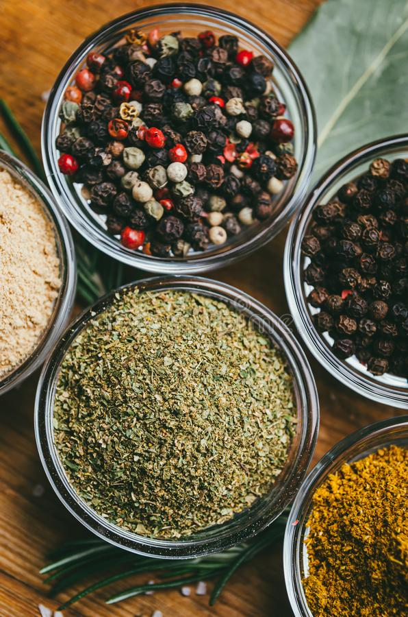 Variety of spices in round glass bowls - ground ginger, hops-suneli, kari, black pepper and a mixture royalty free stock image