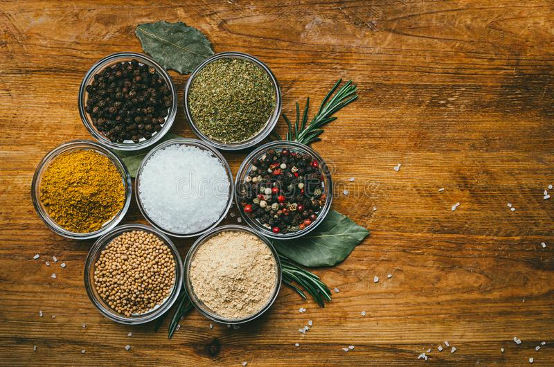 Variety of spices in round glass bowls - ground ginger, hops-suneli, kari, black pepper and a mixture royalty free stock photo