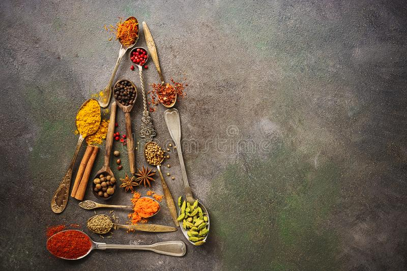 A variety of spices in spoons in the shape of a Christmas tree on a dark rustic background. Abstract christmas tree. Top view, royalty free stock image