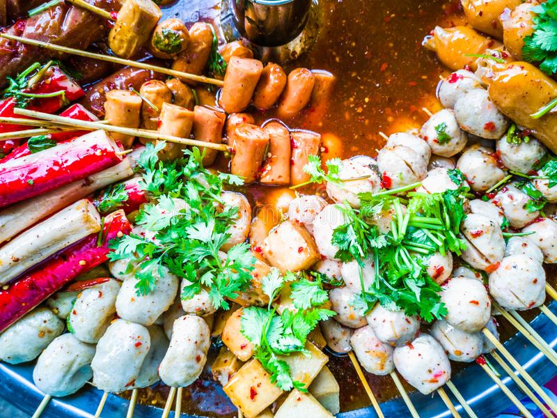 Variety of streamed sausages and meatballs dipped in hot and spicy chilli sauce. Thai style street food, variety of streamed sausages and meatballs dipped in hot stock photography