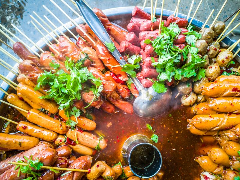 Variety of streamed sausages and meatballs dipped in hot and spicy chilli sauce. Thai style street food, variety of streamed sausages and meatballs dipped in hot royalty free stock photo