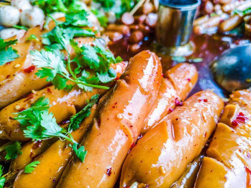 Variety of streamed sausages and meatballs dipped in hot and spicy chilli sauce. Thai style street food, variety of streamed sausages and meatballs dipped in hot royalty free stock photography