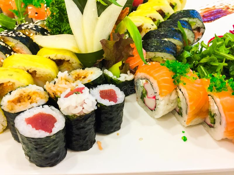 Variety of sushi rolls on a white plate stock photo