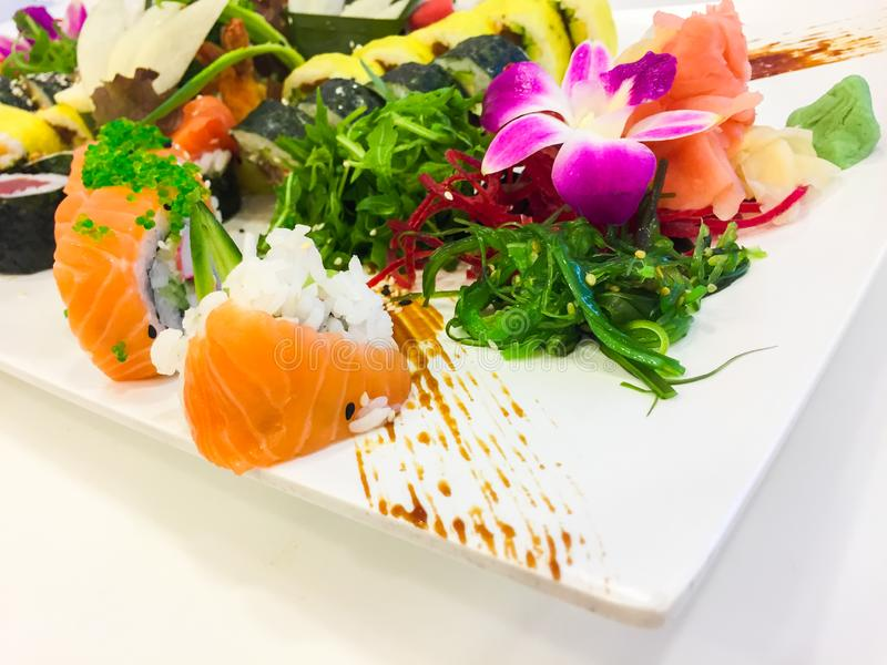 Variety of sushi rolls on a white plate stock images