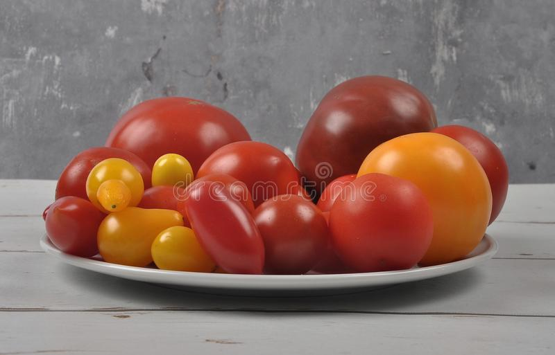 Variety of tomato cultivars on plate and wood royalty free stock photo