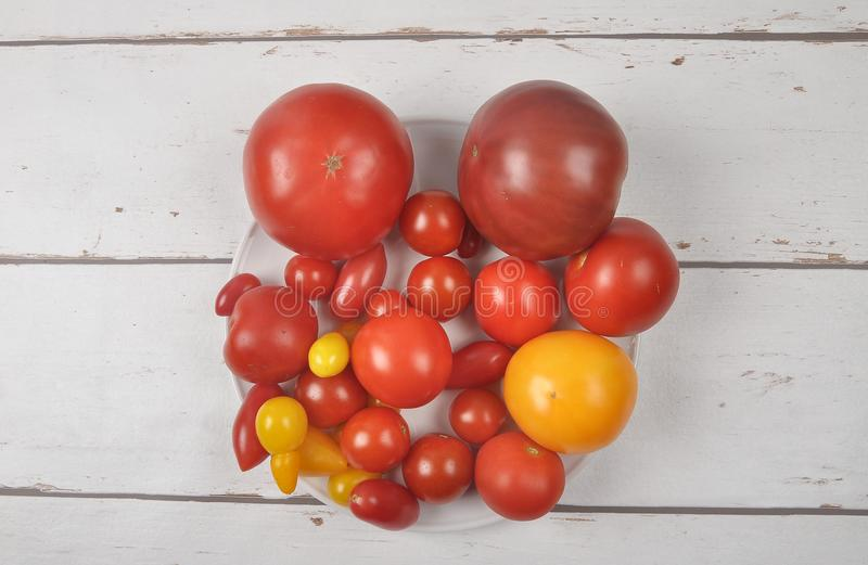 Variety of tomato cultivars on plate and wood stock image
