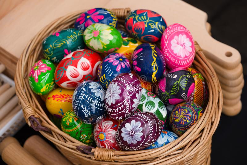 Painted easter eggs for sale at craft market. Variety of traditionally painted Easter eggs in a wicker basket for sale at a craft market royalty free stock image