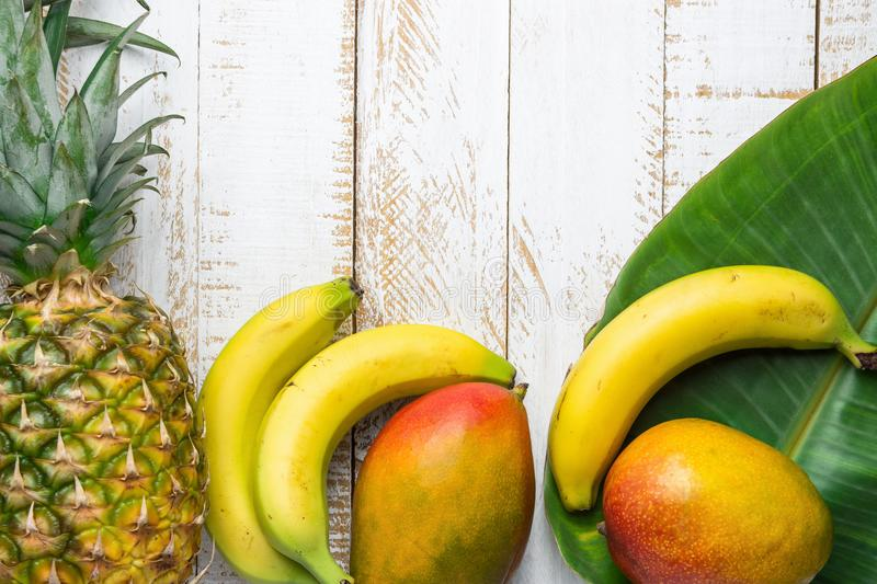 Variety of Tropical Fruits Pineapple Mango Bananas on Large Palm Leaf on White Planked Wood Background. Healthy Diet Vacation. Travel Vitamins Concept. Poster stock photos