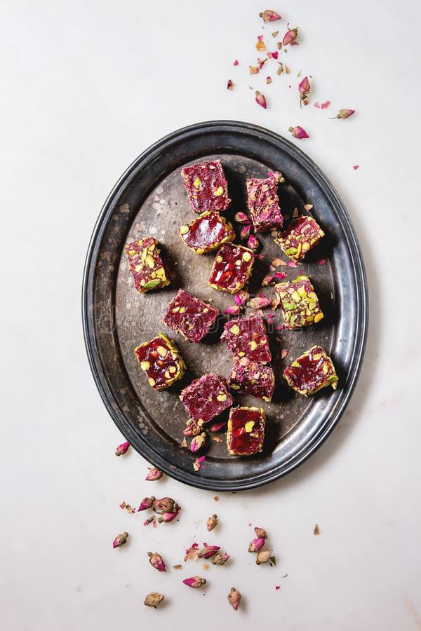 Variety of Turkish Delight. Variety of traditional turkish dessert Turkish Delight different taste and colors with rose petals and pistachio nuts on vintage tray stock image