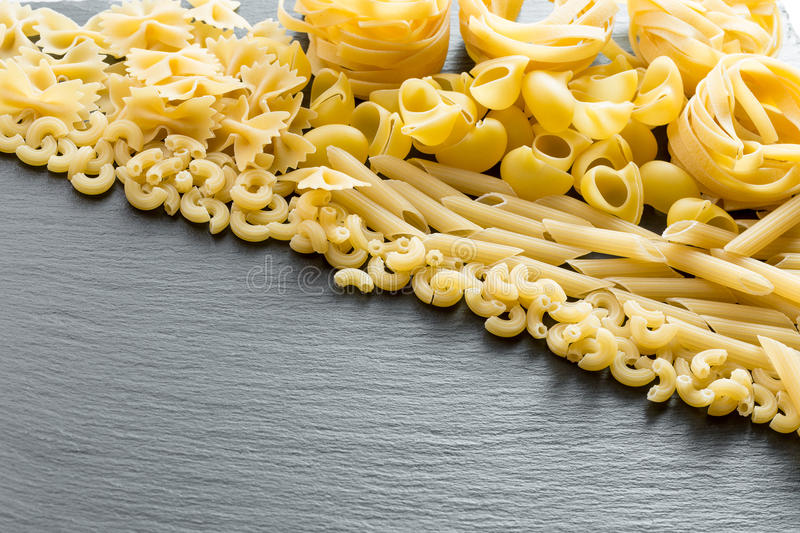 Variety of types and shapes of Italian pasta on a dark stone background.  stock image