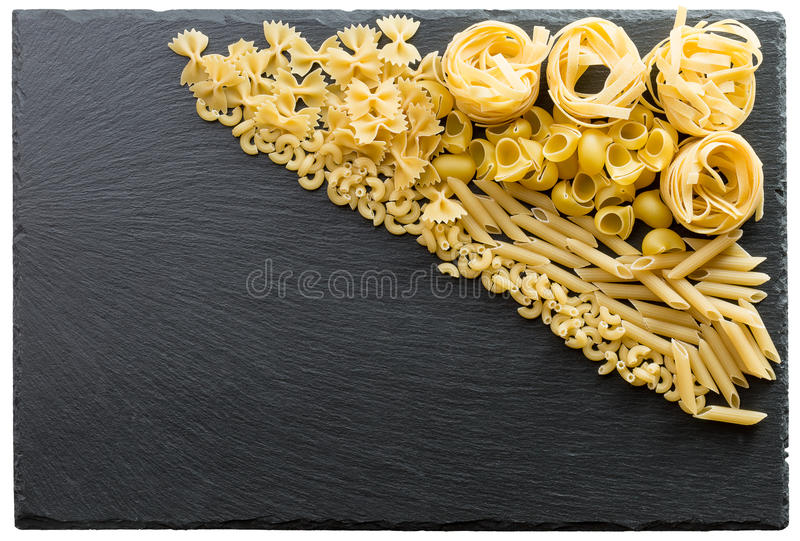 Variety of types and shapes of Italian pasta on a dark stone background.  royalty free stock photos