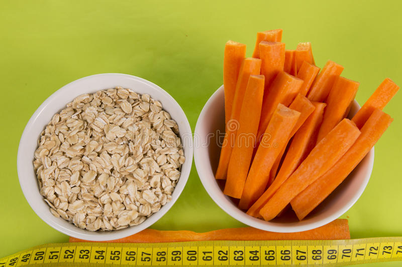 A variety of useful vegetables. Fresh carrots and oatmeal, centimeter on a green background royalty free stock image