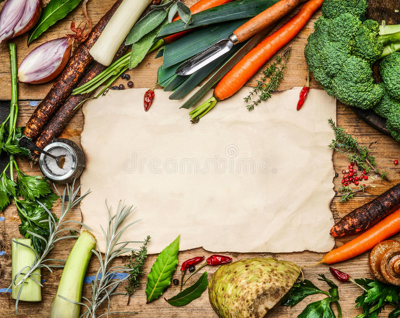 Variety of vegetables ingredients for soup or broth cooking around blank sheet of paper on rustic wooden background, top view. stock photography
