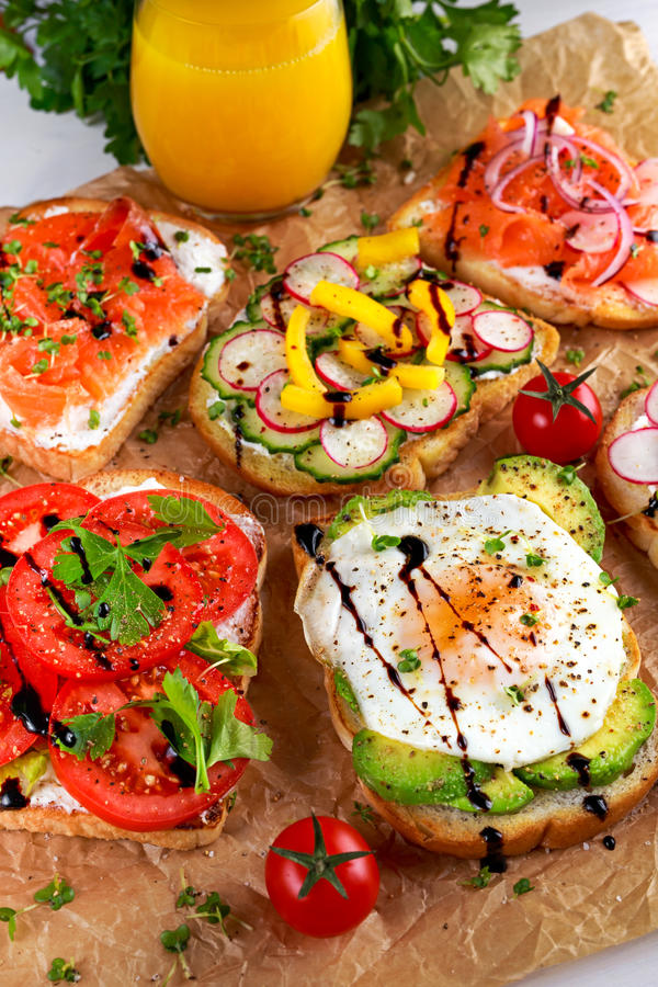 Variety of vegetarian toast sandwiches with salmon, raddish, tomatoes, cucumber, avocado,fried egg and sweet pepper.  stock images