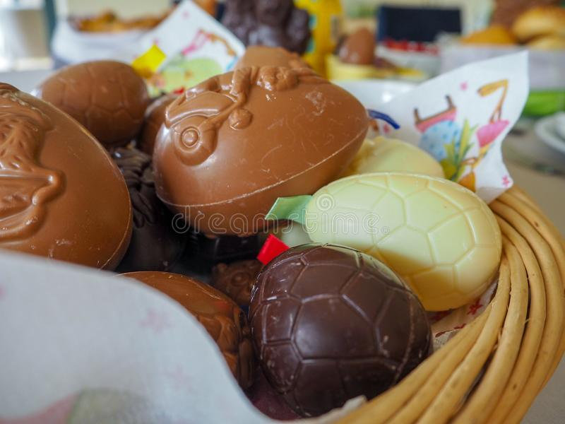 Variety of white, brown and dark chocolate easter eggs in a wicker basket for an easter brunch royalty free stock images