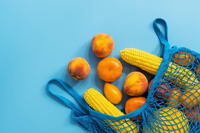 A variety of yellow fruits and vegetables in a cotton mesh bag on a blue background - melon, mandarin, peach, tomato, corn. Flat royalty free stock photos