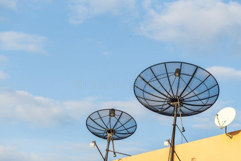 Vario antena parabólica instalada en el tejado de la casa con el cielo azul foto de archivo libre de regalías
