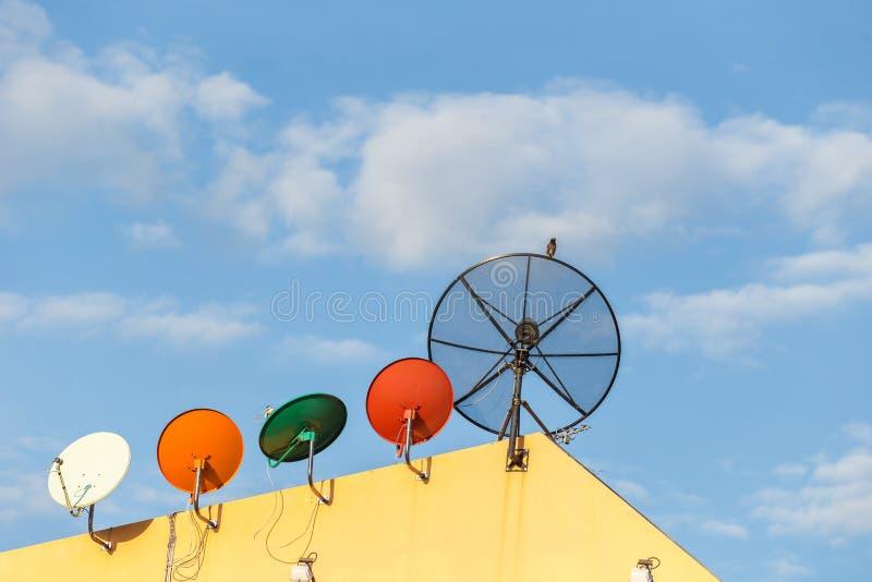 Vario antena parabólica instalada en el tejado de la casa con el cielo azul imagen de archivo libre de regalías