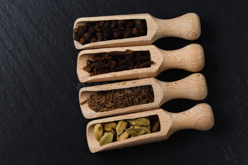 Vario delle spezie e delle erbe in cucchiai di legno Disposizione piana delle spezie sulla pietra nera immagine stock libera da diritti