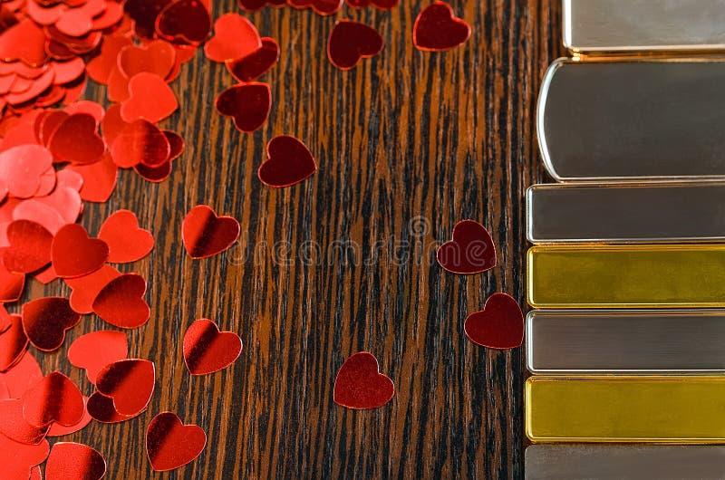 Vario encantos del oro y de la plata en a en un fondo superficial de madera con los pequeños corazones decorativos brillantes roj stock de ilustración