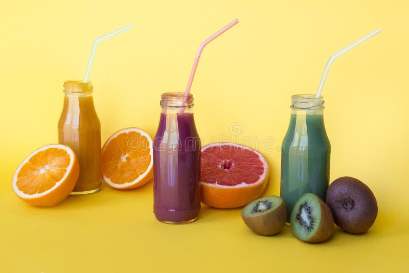 Vario genere di frullati o di succhi in bottiglie, concetto dell'alimento di dieta sana su fondo giallo fotografia stock