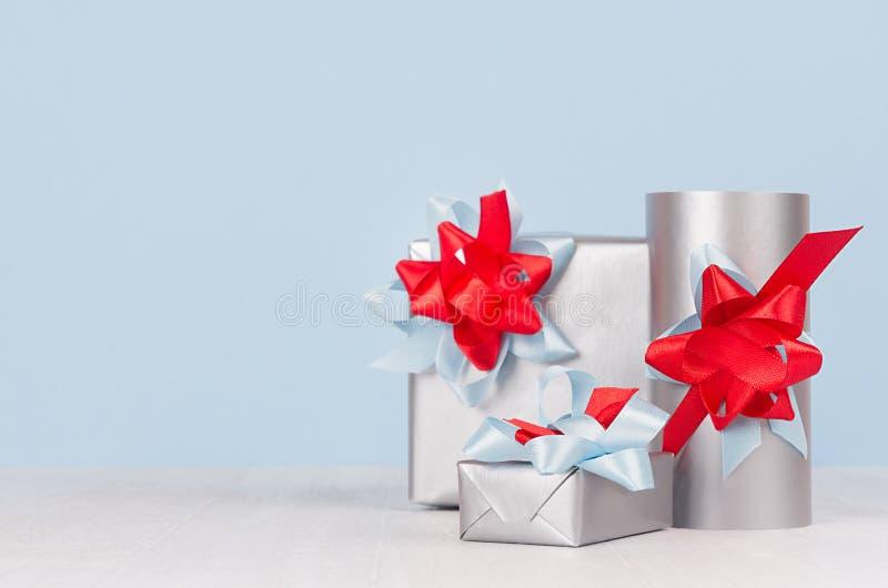 Vario primo piano d'argento dei contenitori di regalo di natale festivo luminoso con i nastri di seta rossi e blu sulla tavola di immagini stock
