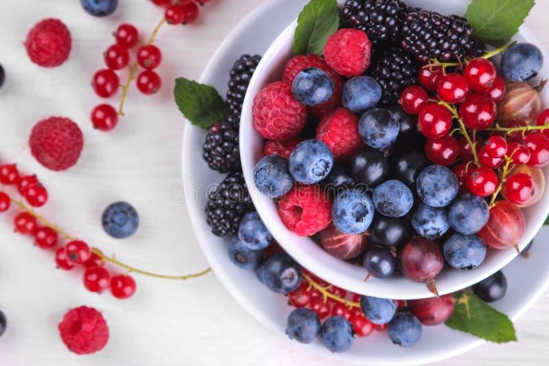 Vario primo piano fresco delle bacche compreso i mirtilli, i lamponi, le more e l'uva passa in una tazza bianca su una parte post fotografia stock