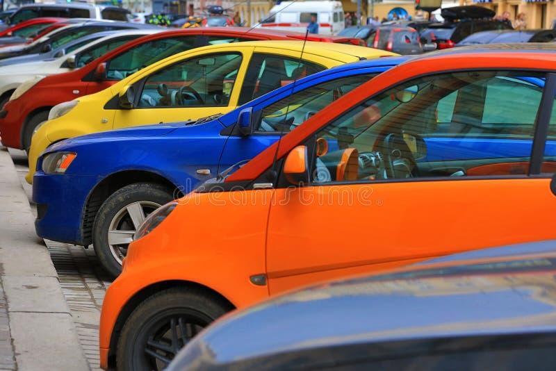 Variopinti parcheggio sulla via, automobili gialle, blu, rosse, arancio immagine stock