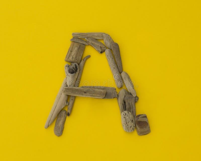` Variopinto della lettera un ` fatto dei bastoni di legno su fondo giallo fotografia stock