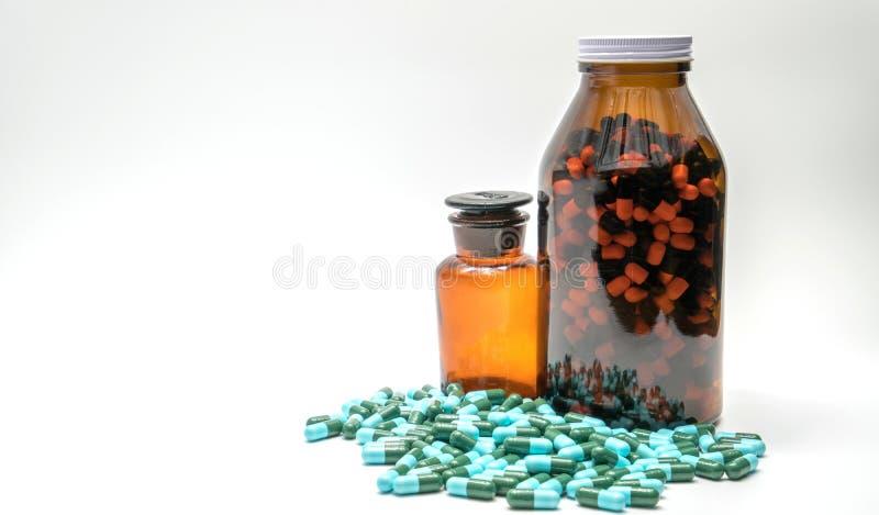 Variopinto delle pillole antibiotiche della capsula della medicina e di due bottiglie ambrate, farmacoresistenza fotografia stock libera da diritti