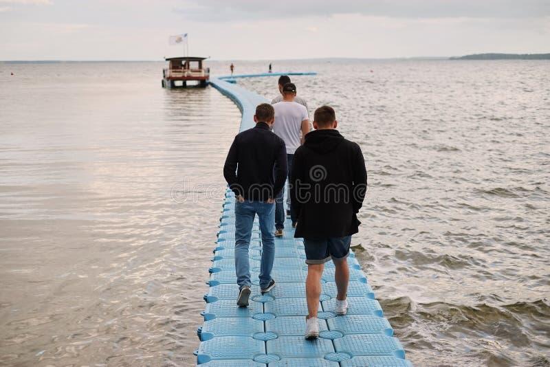 varios amigos masculinos caminan a lo largo de un muelle plástico del embarcadero con el espacio de la copia, detallan de caminar imágenes de archivo libres de regalías