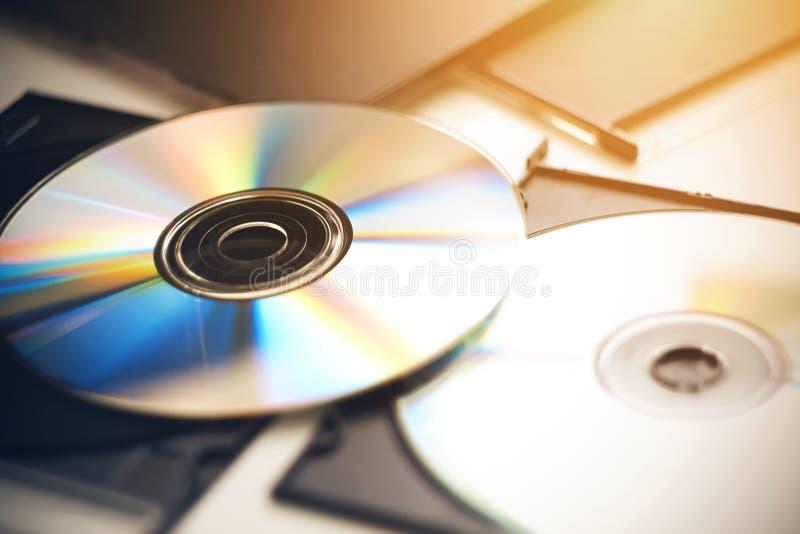 Varios Cdes mienten en una tabla blanca en sus cajas negras imagenes de archivo