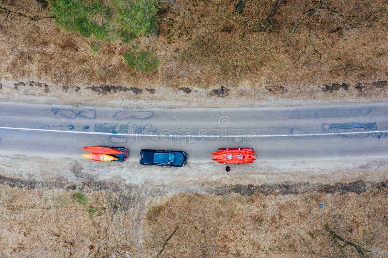 Varios coches con los kajaks en la baca que conduce en el camino entre árboles imágenes de archivo libres de regalías