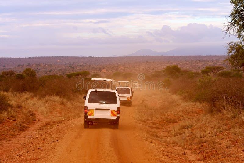 Varios coches del safari en Kenia en África, arena roja y montañas foto de archivo